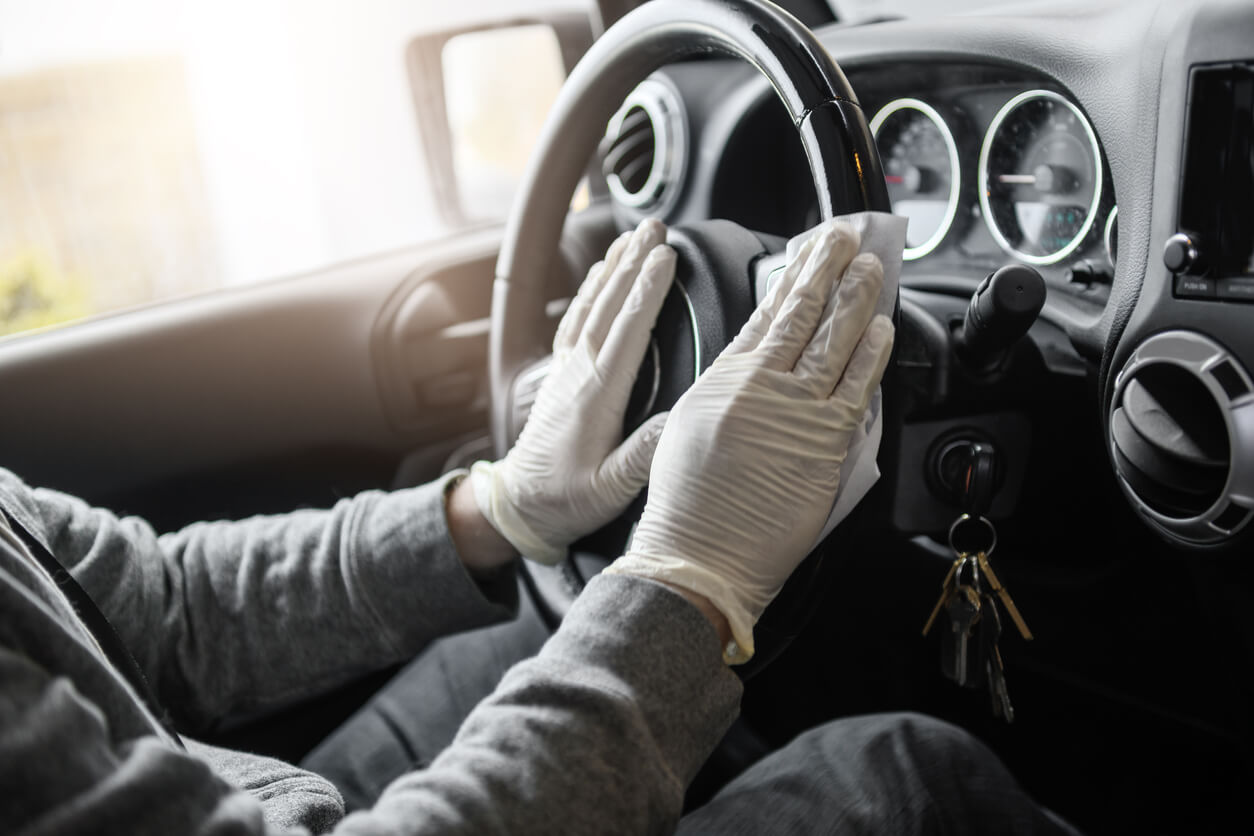 Man following social distancing guidelines, wiping down his car.